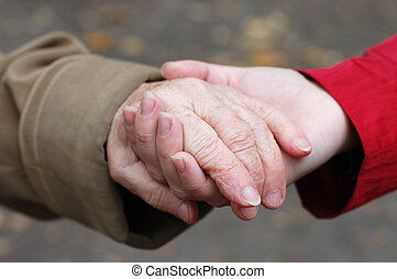 closeup of a grandfather holding his grand daughter hand