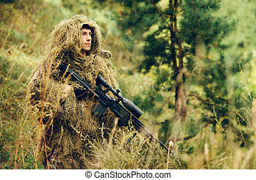 sniper soldier stands with arms and looking at the target -...