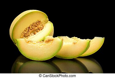 Melon galia notched with slices isolated black in studio -...