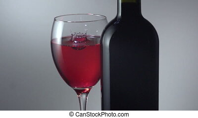 drop in a glass of red wine - Slow motion. Red wine being...