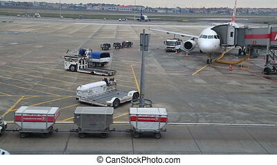Airplane docked at the gate, being refueled, boarded and...