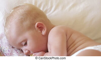 child eat corn lying on a bed