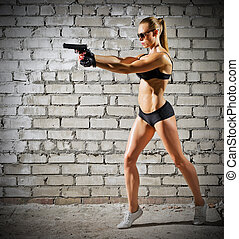 Muscular woman with gun on brick wall (normal version) -...
