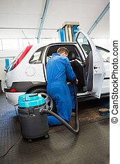 Mechanic vacuuming the car interior at the repair garage