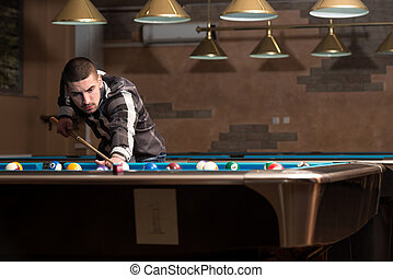 Male Pool Player - Young Man Lining To Hit Ball On Pool...