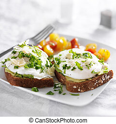 toast with poached eggs, avocado and tomatoes