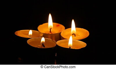 Five small burning candles against a dark background