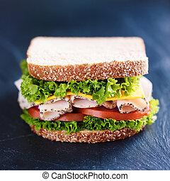 deli meat turkey sandwich on slate surface