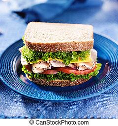 turkey deli meat sandwich on blue plate