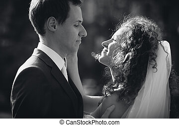 Monochrome portrait of bride and groom looking at each other...