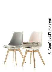 Two modern chairs with a pile of books - Two modern molded...