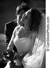 Black and white romantic portrait of groom kissing bride in...