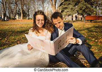 just married couple sitting on grass at park and watching...