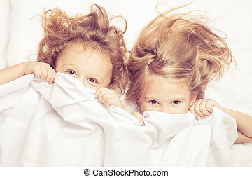 Lovely brother and sister lying in bed at home Concept of...