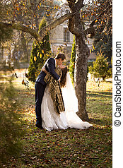 just married couple kissing passionately under tree at...