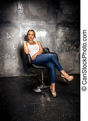 confident blonde woman sitting on chair at grungy room -...