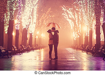 Couple with umbrella kissing at night alley.