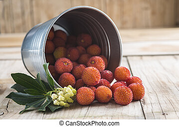 Bucket with ripe arbutus unedo fruits, leaves and flowers on...