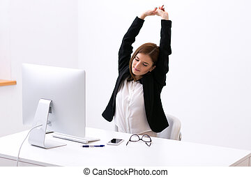 Businesswoman sitting at the table in office and stretching...