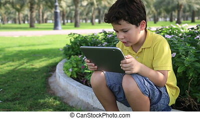 Boy using digital tablet outdoor - Young boy gaming on...