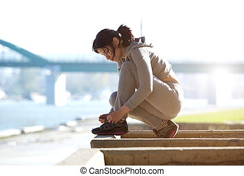 Young woman tying shoe lace before run - Side view of young...