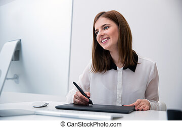 Smiling female photo editor working on computer in office