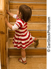 Baby walks upstairs - The young girl walks upstairs