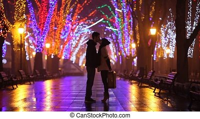 Couple kissing at night alley.\