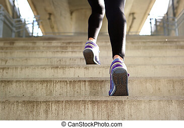 Sports female running up stairs - Rear view sports female...
