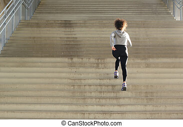 Young female athlete running up stairs - Rear view young...