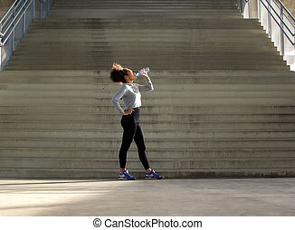 Sport woman drinking water from bottle - Full length...