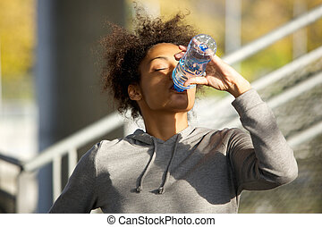 Young sports woman drinking water from bottle - Close up...