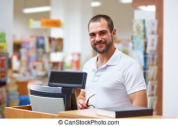 Salesman at the checkout in a bookstore - Young salesman at...