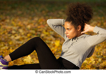 Young woman exercising sit ups outdoors - Portrait of a...