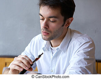 Young man smoking electric cigarette - Close up portrait of...