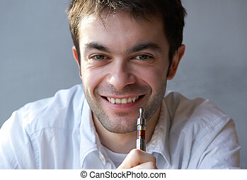 Young man smiling with e cigarette in hand