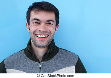 Close up face portrait of a young man smiling against blue...