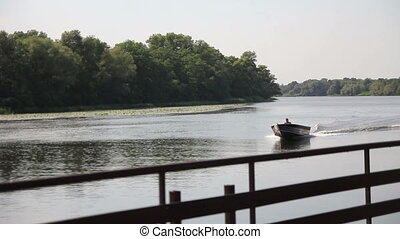 boat on the river - boat floats on the river leaving the...