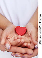 Child and adult hands holding red heart