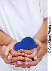 Child and adult hands holding car shaped paper