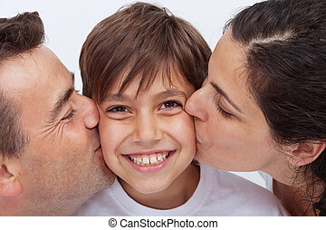 Happy boy having the attention of his parents kissing him -...