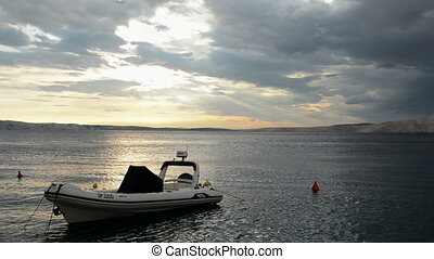 Small motor boat on the sea at sunset