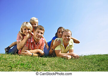 Group of four friends and kids skipping through a park in...