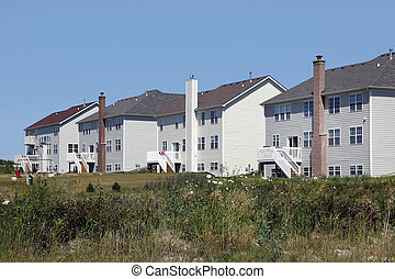 Rear view of large white homes in a rural environment