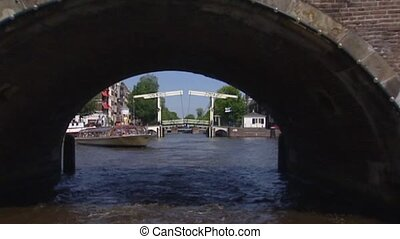Amsterdam cruise canal district under stone bridge + cyclist...