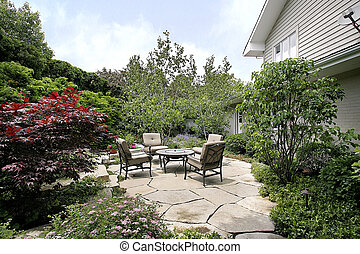 Patio and stone sidewalk with foliage and chairs