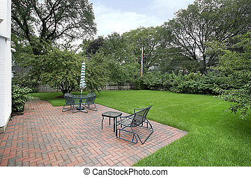 Brick patio and back yard - Brick patio with umbrella and...