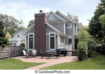 Rear view of luxury home with brick patio