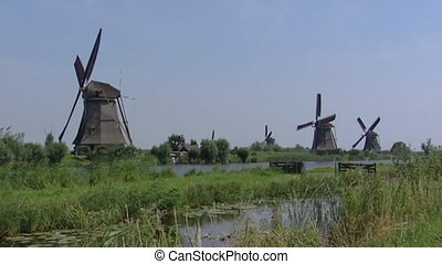 Kinderdijk windmills pumping in polder - wide shot -...