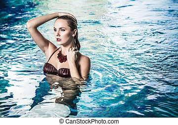 Swimming pool - Young lady in bikini having a good time in...